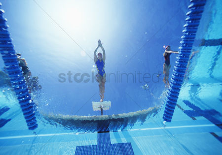 Diving : View of female swimmer diving in swimming pool