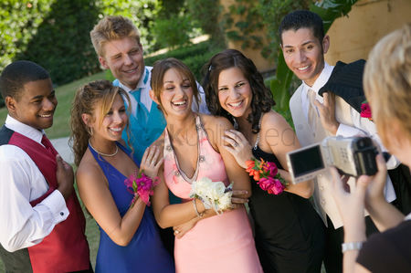 Dance : Well-dressed teenagers posing for video camera outside school dance