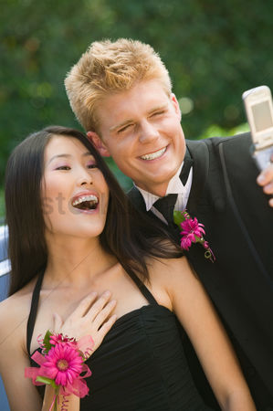 Dance : Well-dressed teenagers taking photo with camera phone outside