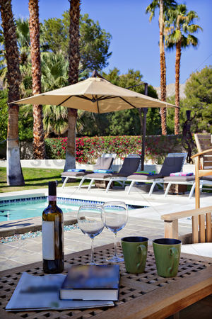 Wine bottle : Wine and wineglasses by poolside