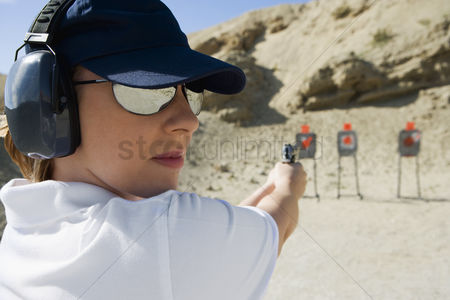 Firing : Woan aiming hand gun at firing range