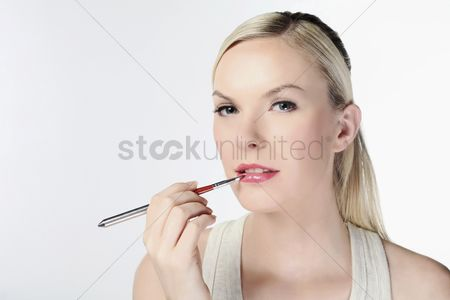 British ethnicity : Woman applying lip color using lip brush