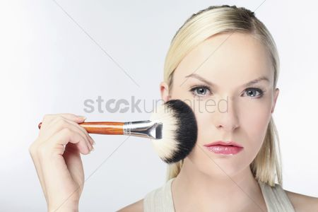 British ethnicity : Woman applying powder on face with make-up brush