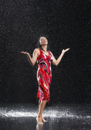Arm raised : Woman arms raised smiling standing in rain