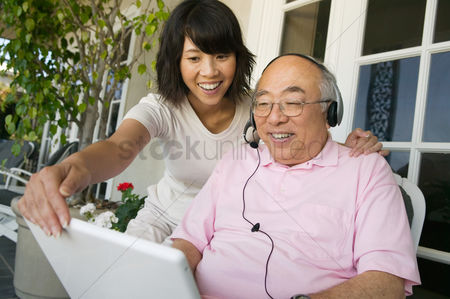 Accessibility : Woman assisting father wearing headset and using laptop on porch