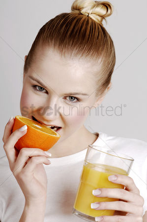 Satisfying : Woman biting an orange while holding a glass of orange juice