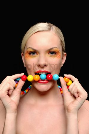 British ethnicity : Woman biting colorful necklace