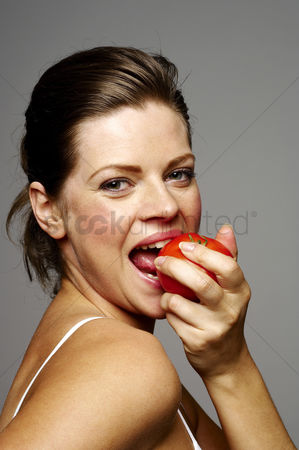 Satisfying : Woman biting tomato
