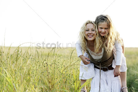 Grass : Woman carrying girl