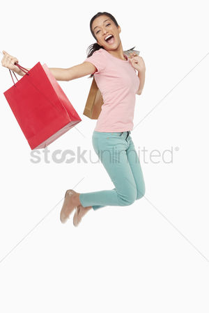 Malaysian indian : Woman carrying shopping bags  jumping mid air