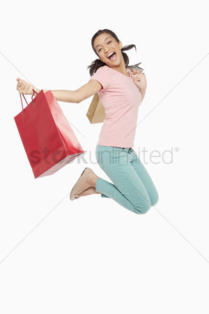 Excited : Woman carrying shopping bags  jumping mid air