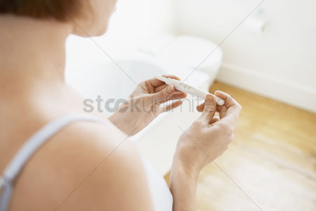 Interior : Woman checking pregnancy test kit mid-section focus on hands