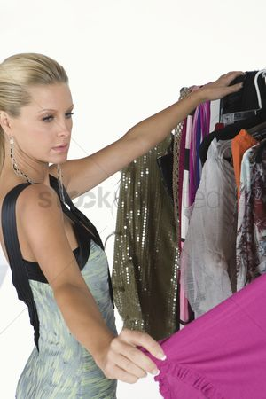 Choosing : Woman chooses from a selection of items on a clothes rail