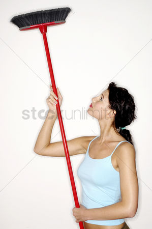 Tidy : Woman cleaning ceiling with a broom