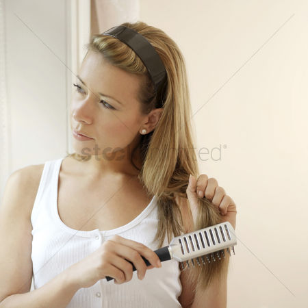 Pensive : Woman combing her hair