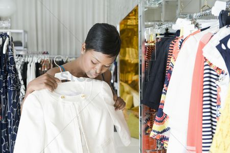 Choosing : Woman considers white jacket in clothes store