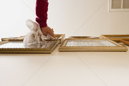 Housewife : Woman dusting picture frames