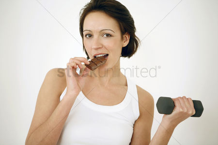 Strong : Woman eating chocolate bar while lifting dumbbell