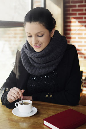 Cold temperature : Woman enjoying a cup of coffee at the cafe