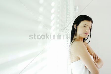 Cheerful : Woman folding her arms while leaning against window blinds