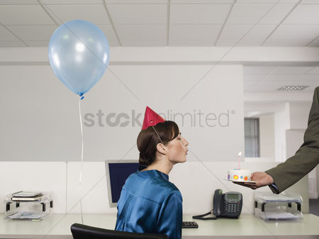 Blowing : Woman having birthday party in office