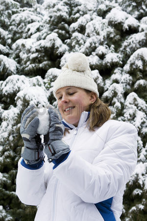 Coldness : Woman having fun playing snowball