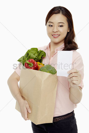 Selection : Woman holding a bag of groceries and a shopping list