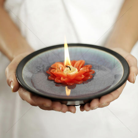 Refreshment : Woman holding a bowl of water with lit candle floating on it