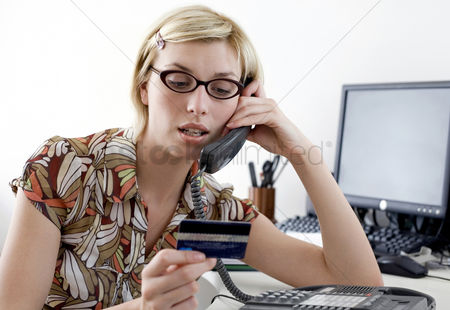 Accessibility : Woman holding a credit card while talking on the phone