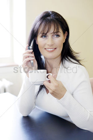 Cell phone : Woman holding a cup while talking on the mobile phone
