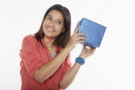 Malay : Woman holding a gift box close to her ears