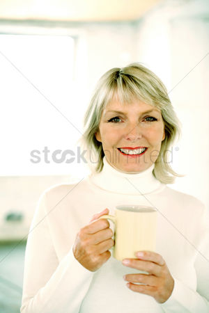 Flavour : Woman holding a glass while smiling at the camera
