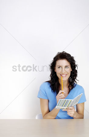 Thought : Woman holding a pencil and a note book thinking