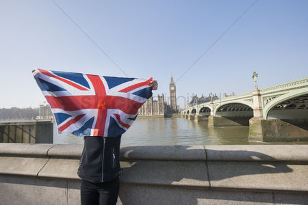 Flag : Woman holding british flag in front of face against big ben at london  england  uk
