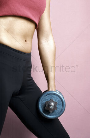 Strong : Woman holding dumbbell