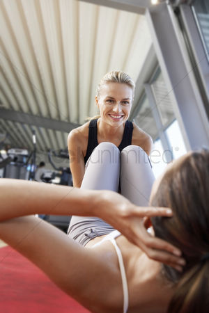 Fitness : Woman holding legs of woman doing sit ups in health club