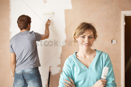 Paint brush : Woman holding paint brush next to man painting interior wall