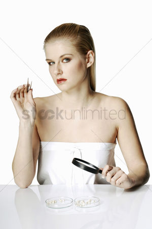 Careful : Woman holding tweezers and magnifying glass