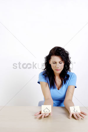 Thought : Woman holding two papers with heart shape and a question mark