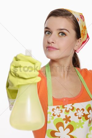 Housewife : Woman in apron using spray bottle