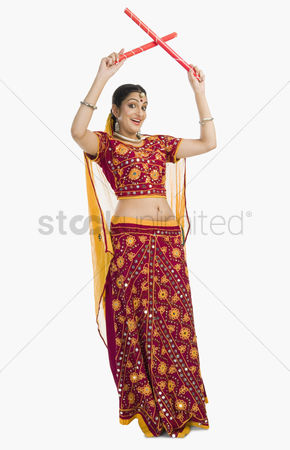 Dance : Woman in lehenga choli performing dandiya dance
