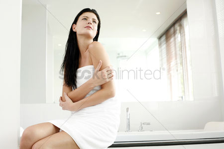 Satisfying : Woman in towel sitting on the bathtub ledge