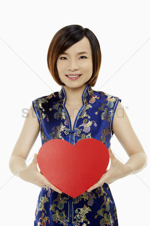 Lunar new year : Woman in traditional clothing holding up a red heart