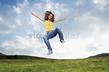Remote : Woman jumping for joy in mountain meadow front view