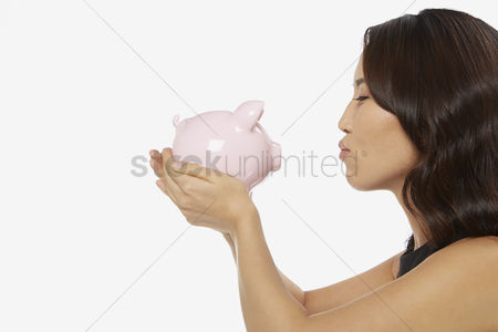 Kissing : Woman kissing a piggy bank