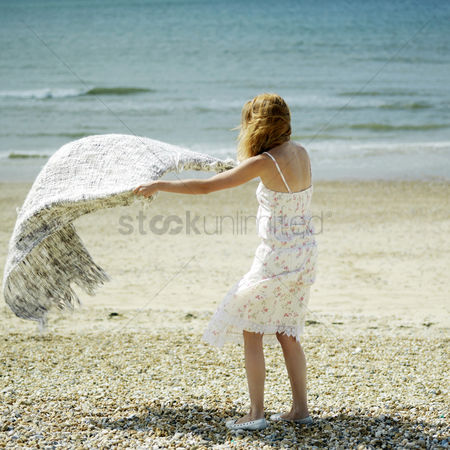 Blowing : Woman laying down picnic blanket on the beach
