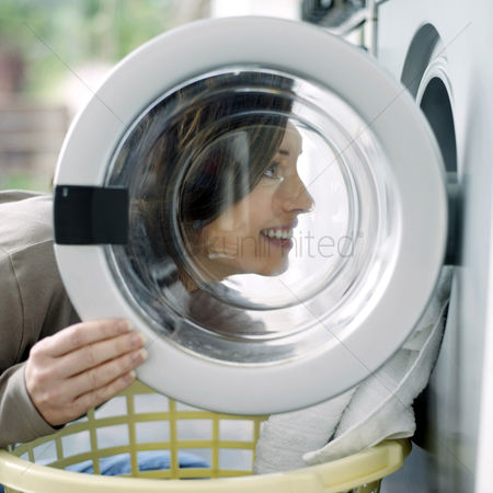 Housewife : Woman loading clothes into the washing machine