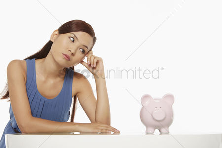 China : Woman looking at a piggy bank  contemplating