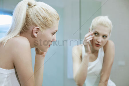 Examination : Woman looking at her reflection in the mirror
