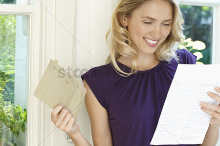 Satisfaction : Woman looking at letter looking happy